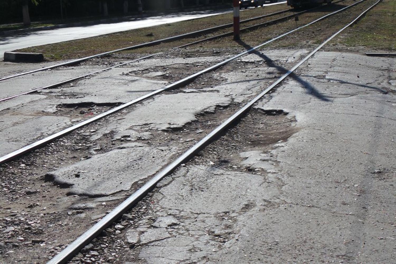 Эти рельсы возвышаются над дорогой из-за разрушения асфальта. Источник: {mosaica.ru}(http://mosaica.ru/news/obshchestvo/2014/08/14/35150-3)