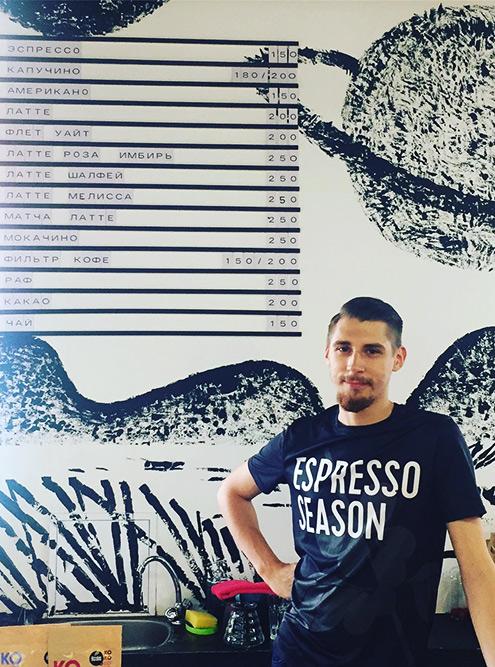 Меню на задней стене кофейни и бариста Илья