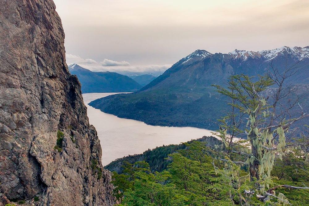 Повсюду заснеженные горные пики. Многие деревья покрыты сухим свисающим мхом