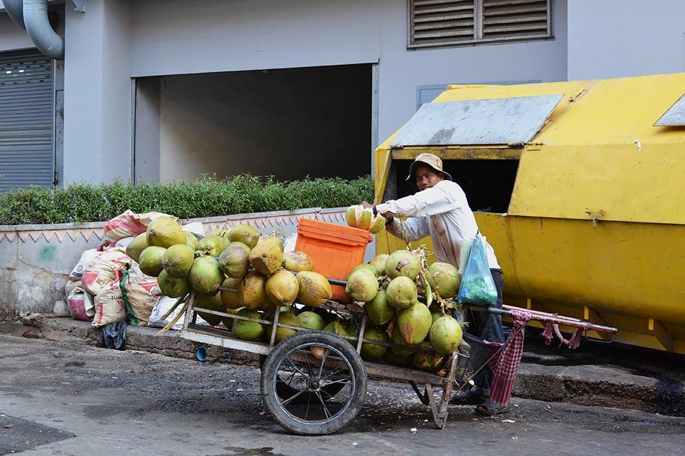 Уличный продавец кокосовой воды в два приема срезает верхушку кокоса и подает освежающий напиток