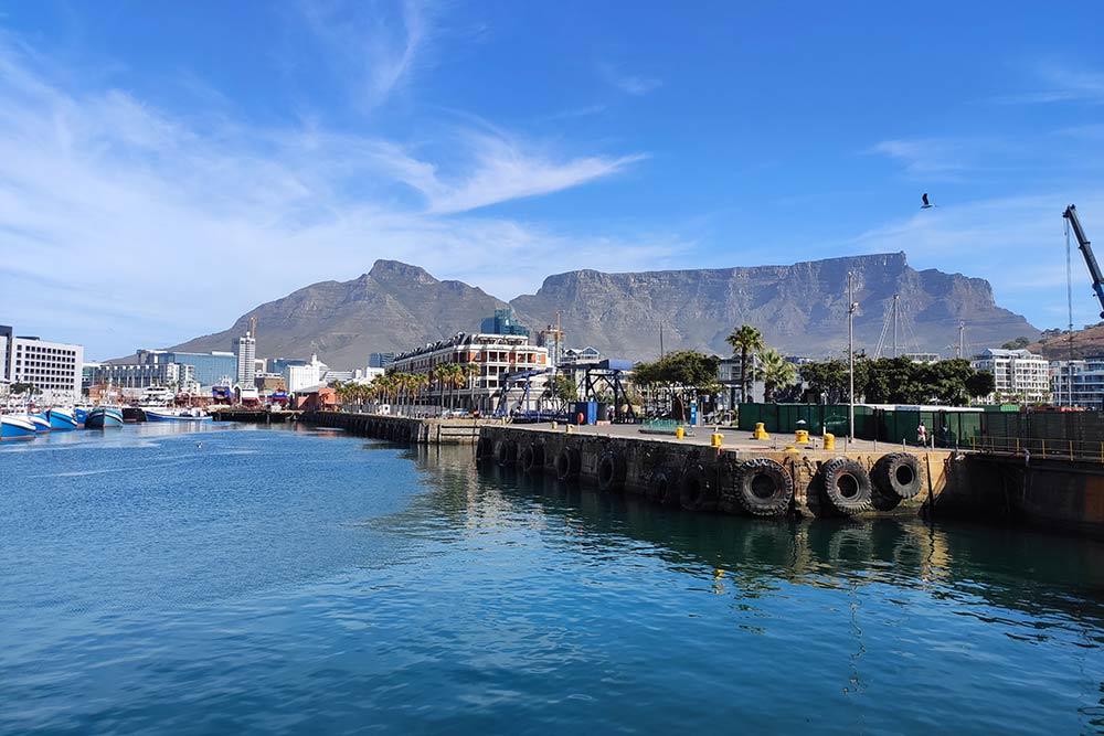 Порт Кейптауна и Столовая гора на заднем плане, ее высота — 1087 метров. Это главный символ Кейптауна, веками ее силуэт на горизонте говорил мореплавателям, что впереди долгожданная бухта, где можно пополнить запасы еды и пресной воды
