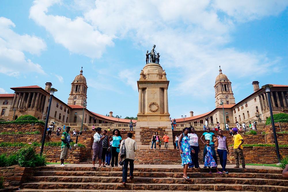Местные жители гуляют у здания правительства ЮАР. Это город Претория — административная столица Южной Африки