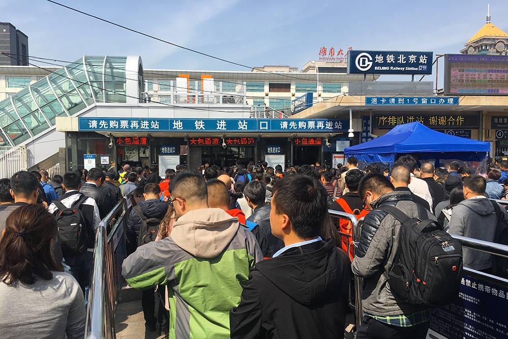 Очередь на вход в метро у центрального вокзала в Пекине. Железные заборы направляют потоки людей к разным входам, чтобы избежать хаоса