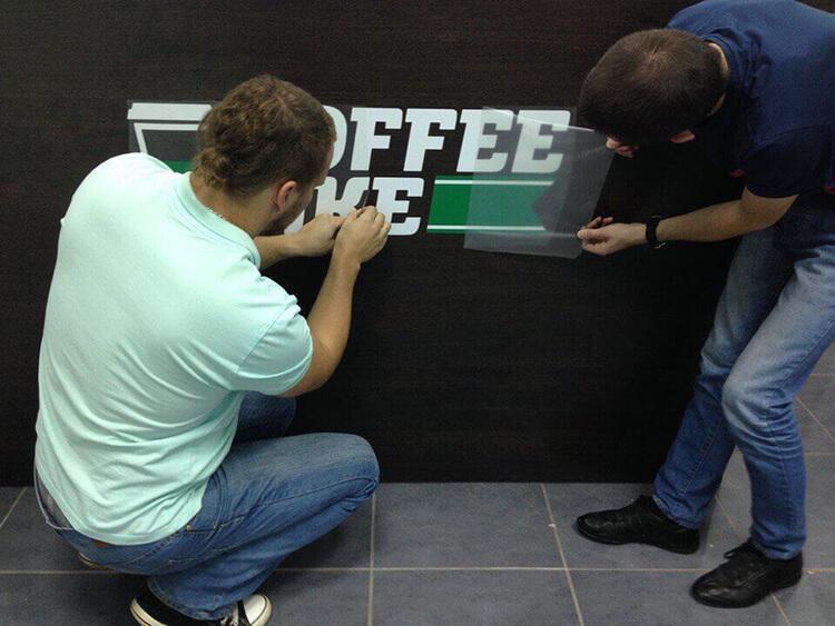 Никита с коллегой клеят логотип на первый кофе-бар