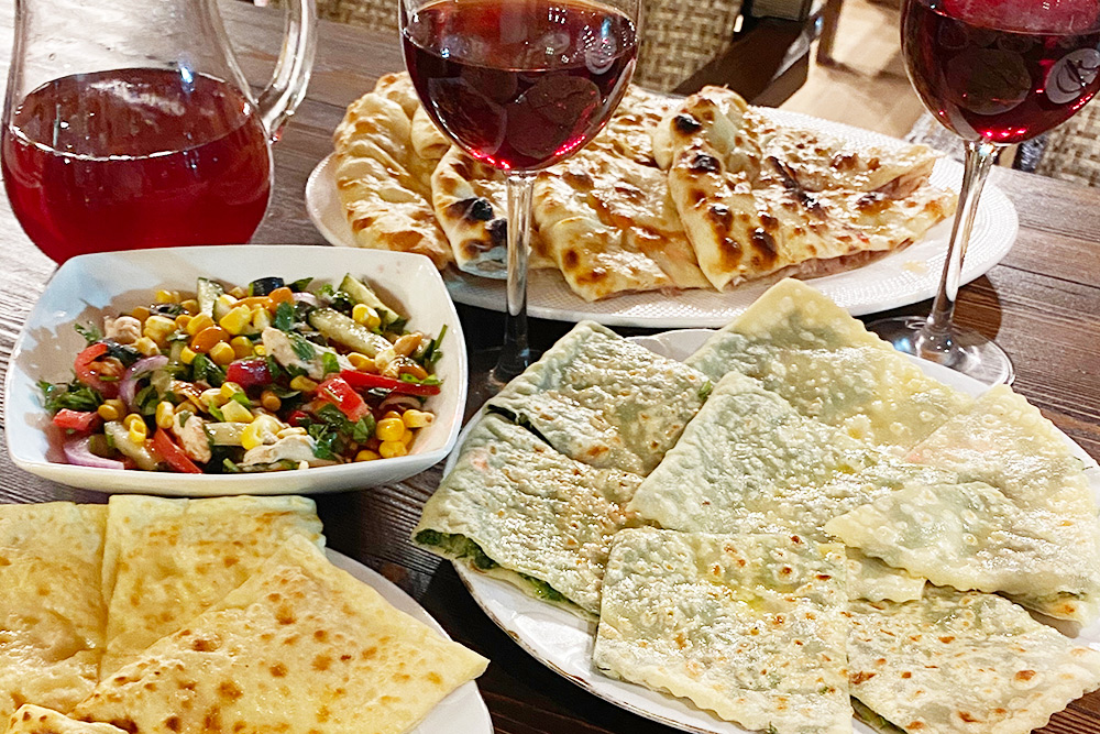 Три вида чуду — с мясом, зеленью и сыром, греческий салат, фирменный салат «Крепость», компот в графине, вино в бокалах. За все мы заплатили 1730<span class=ruble>Р</span>