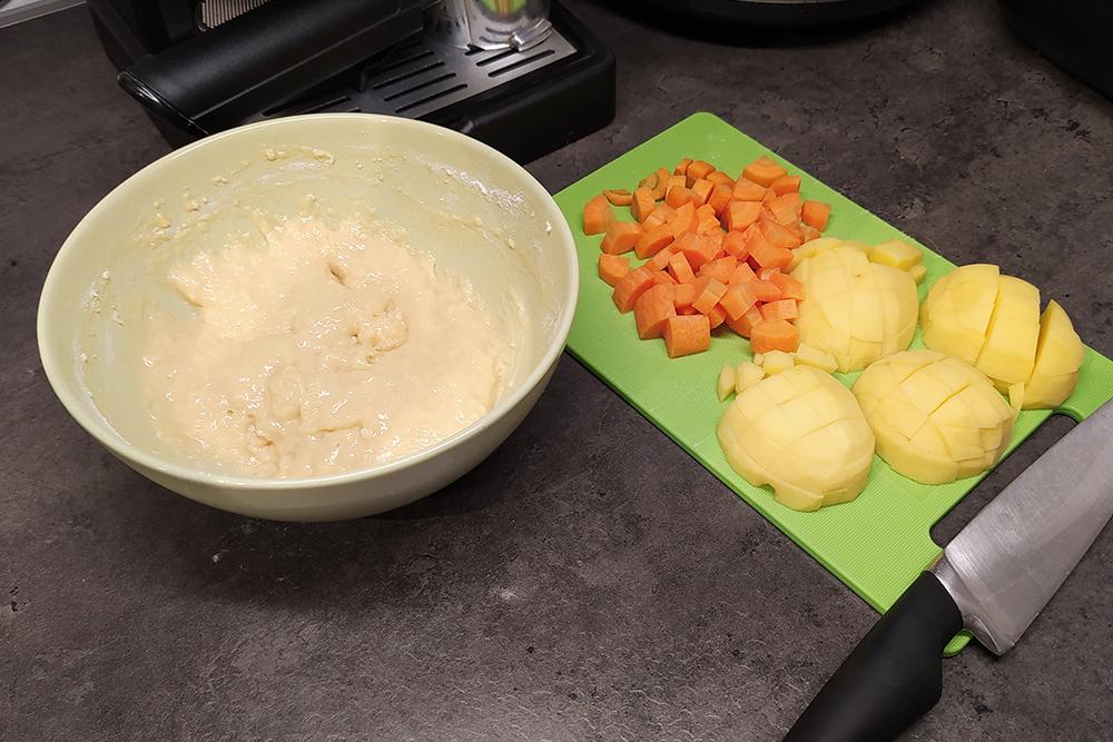 Пока закипает вода, чищу картошку и морковку, замешиваю тесто на клецки. После закипания дважды снимаю пену и оставляю слабо кипеть на 40 минут