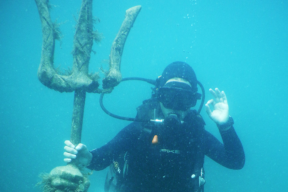 Погружение на Черном море. Одной рукой держусь за трезубец статуи в морском музее, другой — показываю, что у меня все хорошо