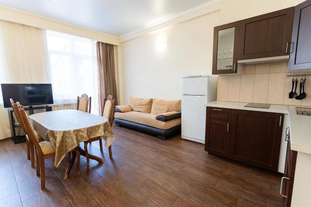 Наша студия в комплексе «Вершина». В этойже комнате стоит двуспальная кровать и еще один диван. В апартаментах есть собственная ванная, коридор и балкон. Источник: booking.com