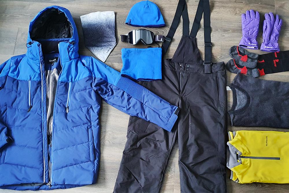 Горнолыжная экипировка: непродуваемые куртка и брюки с высоким поясом, балаклава, шапка, очки, воротник, перчатки, носки, термобелье, флисовая кофта