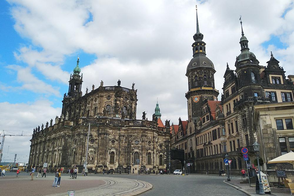 Здание со статуями слева — Хофкирхе. Внутри — богатые интерьеры, алтарь и копия православной иконы Рублева «Святая Троица». Справа — Дрезденский замок-резиденция и башня Хаусманнстурм