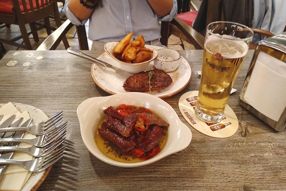 Свиная шея с картофелем и соусом, жареная свинина по-иберийски и немецкое бочковое пиво. Пиво девушке понравилось даже больше чешского. Оно стоит 2,95€ за 0,25 мл. Все блюда на фото — 21€