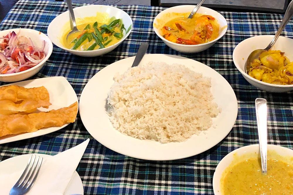 Традиционный шри-ланкийский карри. В тарелках слева направо — пападам, лук с помидорами, стручковая фасоль с карри, креветки с карри, жареная картошка, горох в карри