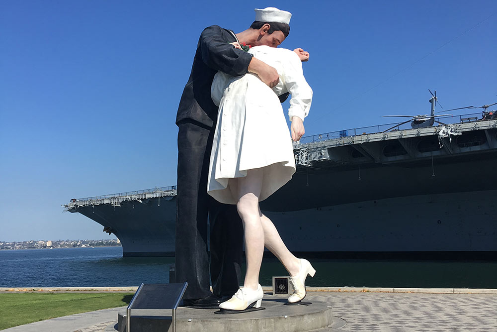 Это скульптура «Безоговорочная капитуляция», аназаднем плане — авианосец USSMidway