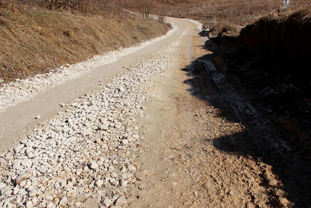 Дорога насыпана пять месяцев назад. Отсыпка «разъехалась», образовались колеи, а справа щебень смешался с грязью
