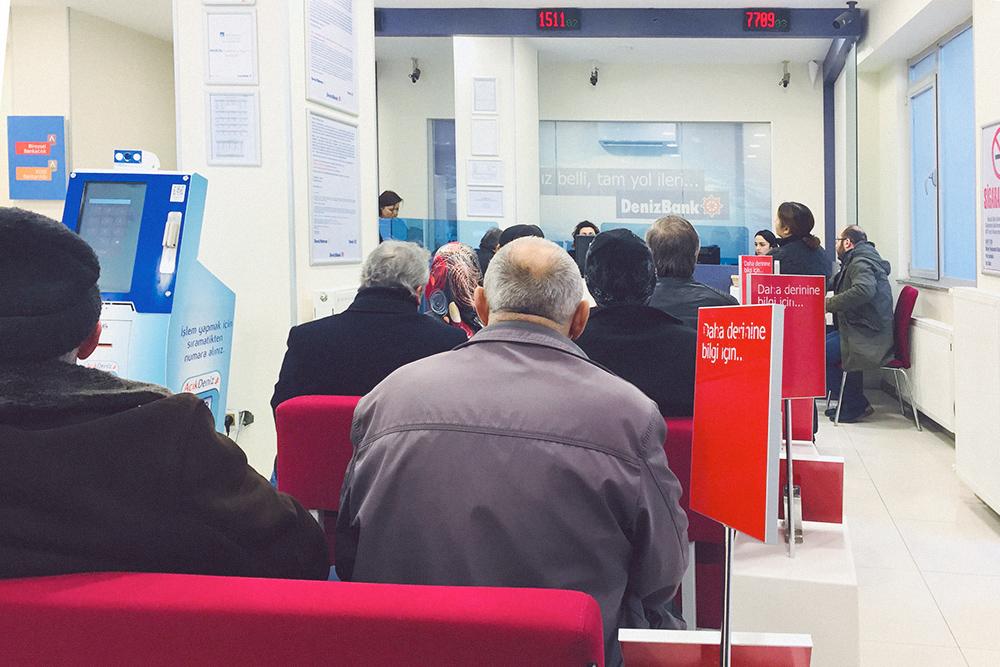 Электронная очередь в банке, все сидят спокойно и ждут свой номер на табло