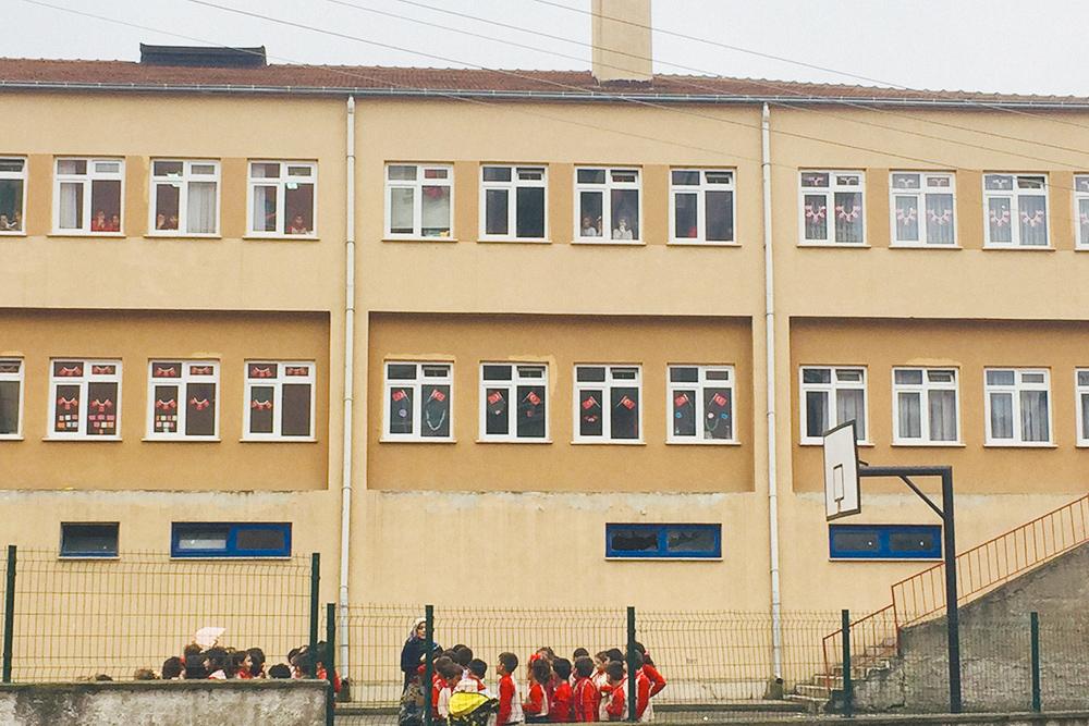 В детях воспитывают патриотизм: окна украшены флагами Турции, каждый ребенок должен знать национальный гимн. На фото — начальная школа, в ней учатся с 1 по 3 класс, потом переходят в другое здание к другим учителям