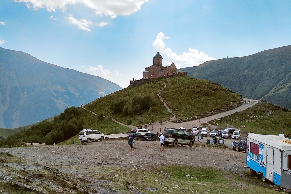 Храм Гергети и стоянка минивэнов. На горе ведутся дорожные работы. Возможно, скоро по дороге можно будет проехать на легковом авто