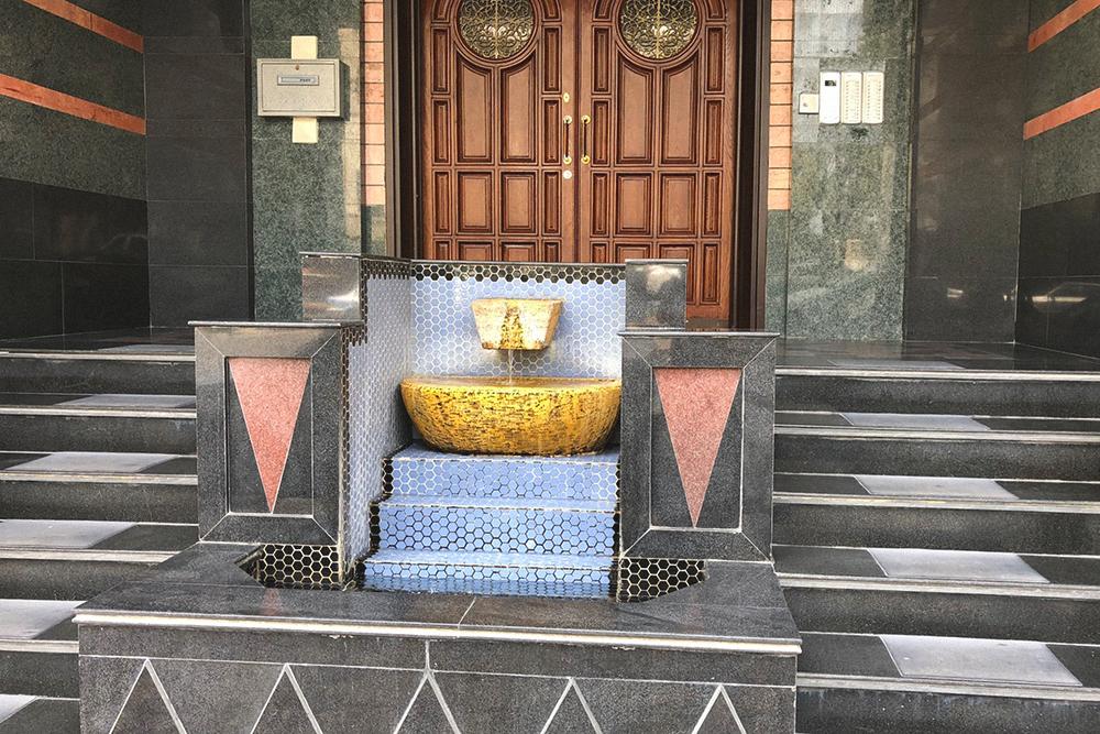 Подъезд жилого дома с фонтаном на соседней улице