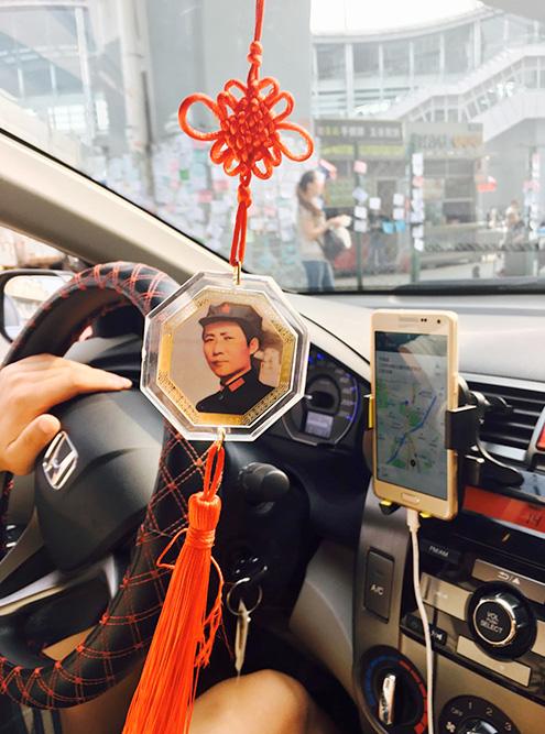 Водители всегда пользуются навигатором, а не сами решают, как удобнее проехать. Этот водитель такси украсил салон портретом Мао Цзэдуна — он все еще в почете в Китае