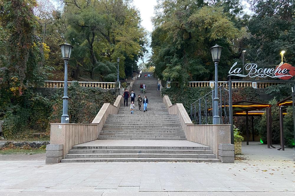 Летом Каменная лестница утопает в зелени, а осенью покрывается золотом — и виноград, что свисает с перил, становится багряным