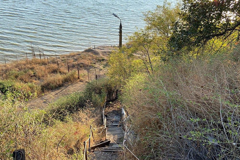 Старая деревянная опасная лестница, по которой жители Богудонии спускаются к морю