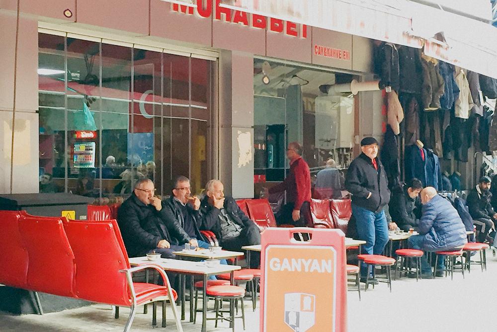 Пенсионеры пьют чай, общаются. Столы и стулья обычно стоят внутри и снаружи заведения