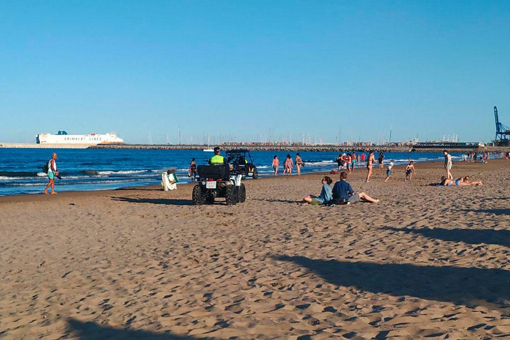 Полицейские перемещаются по пляжу на квадроциклах