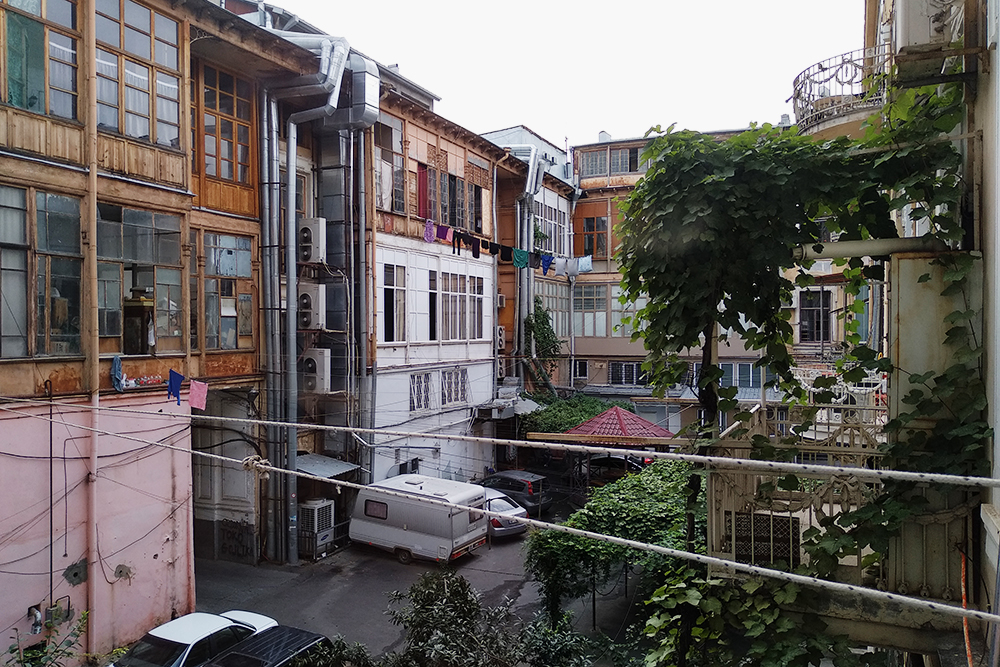 Вид из окна в центре города. Тихий дворик, в котором сушат одежду на веревках