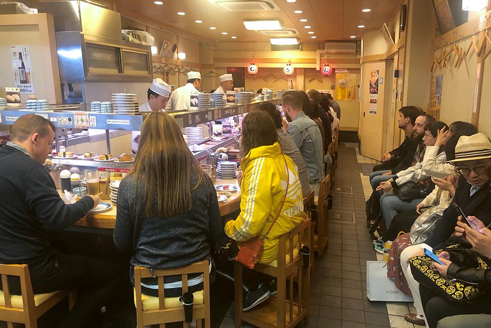 В очереди даже можно сидеть. Справа на фото — очередь на посадку в суши-баре Sushi no Musashi в Киото