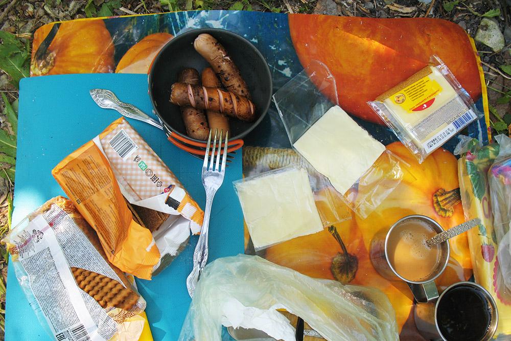 Так выглядит походный обед: клеенка на траве, железные кружки с кофе, крекер, хрустящие хлебцы с плавленым сыром и жареные сосиски. Шпажки для сосисок мы делали из ивовых веток