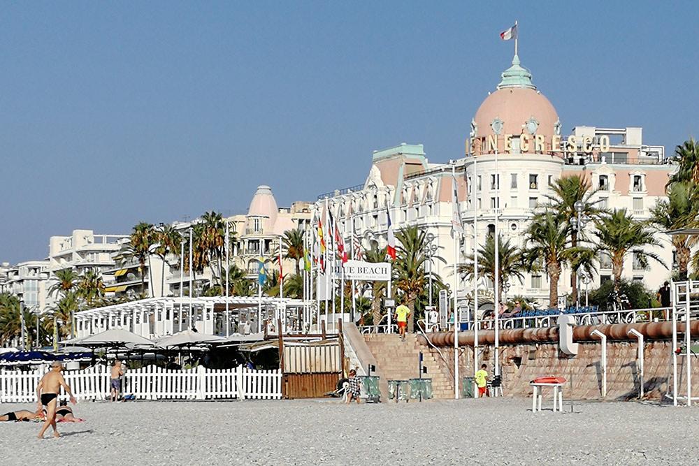 Платный и бесплатный пляж отделены друг от друга белым заборчиком