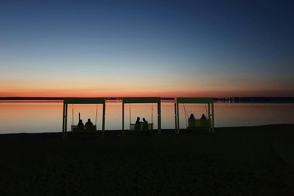 Повечерам парочки провожают закаты, сидя накачелях наАфанасьевском пляже