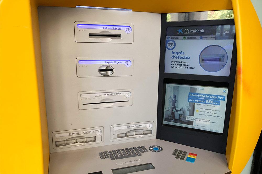 Банкомат CaixaBank. Некоторые испанцы старшего возраста до сих пор пользуются банковской книжкой, длянее предусмотрено верхнее отверстие