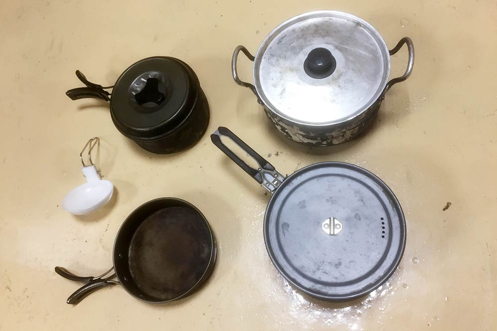 Набор посуды из трех кастрюль и сковородки. Слева складной половник, он был в комплекте с набором посуды