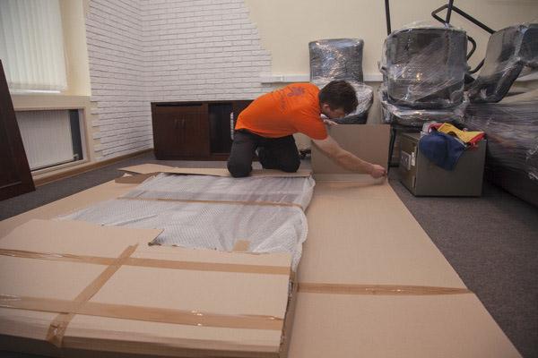 Профессиональный грузчик упаковывает шкаф. Это офисный переезд