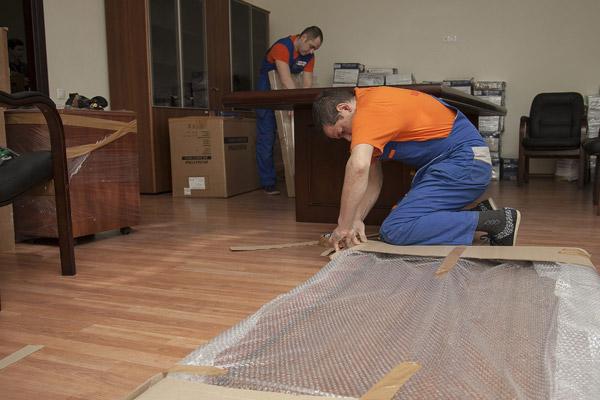 Грузчики упаковывают разобранную мебель. Если не выделить время на разбор и упаковку, то потребуется в два раза больше транспорта