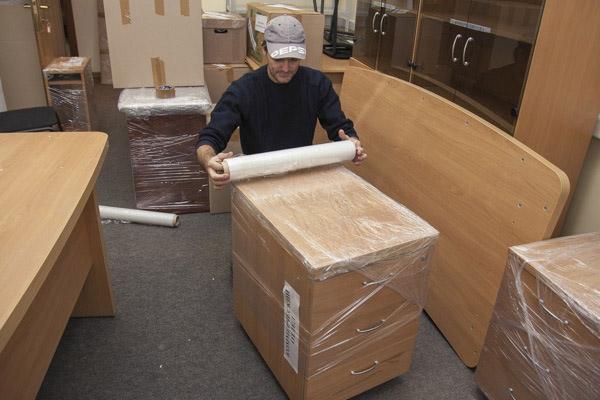 Грузчик упаковывает офисную мебель в пленку, чтобы не обить углы и не поцарапать поверхности. К сожалению, ДСП и МДФ-панели не приспособлены к грузоперевозкам