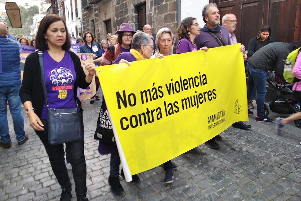 Празднование 8Марта. На плакате написано: «Нет насилию против женщин»