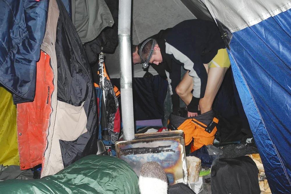 Внутри зимней палатки развешаны куртки: сушатся. Япереодеваюсь назаднем плане