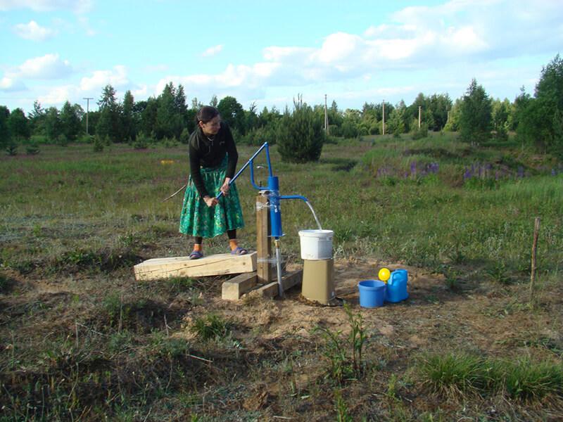 Ольга набирает воду в скважине в 20 метрах от временного жилища