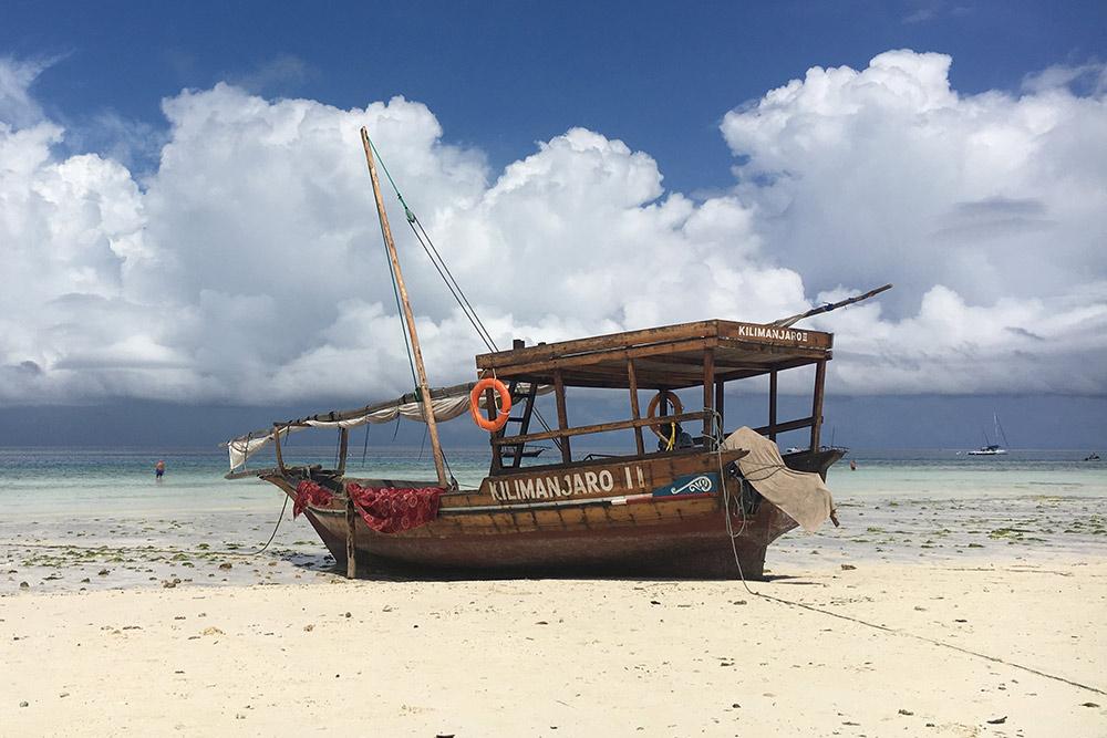 Максимальный отлив на пляже Нунгви: еще утром лодка была погружена в воду, а потом вода ушла далеко, оставив ее на суше. До глубины идти около 50 метров, придется обходить ежей