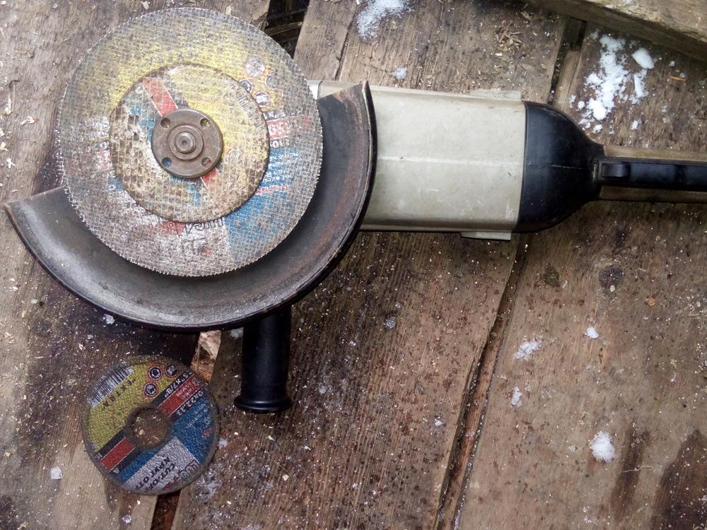 С помощью болгарки Анатолий режет металл: перед сваркой онвыполняет монтажные работы