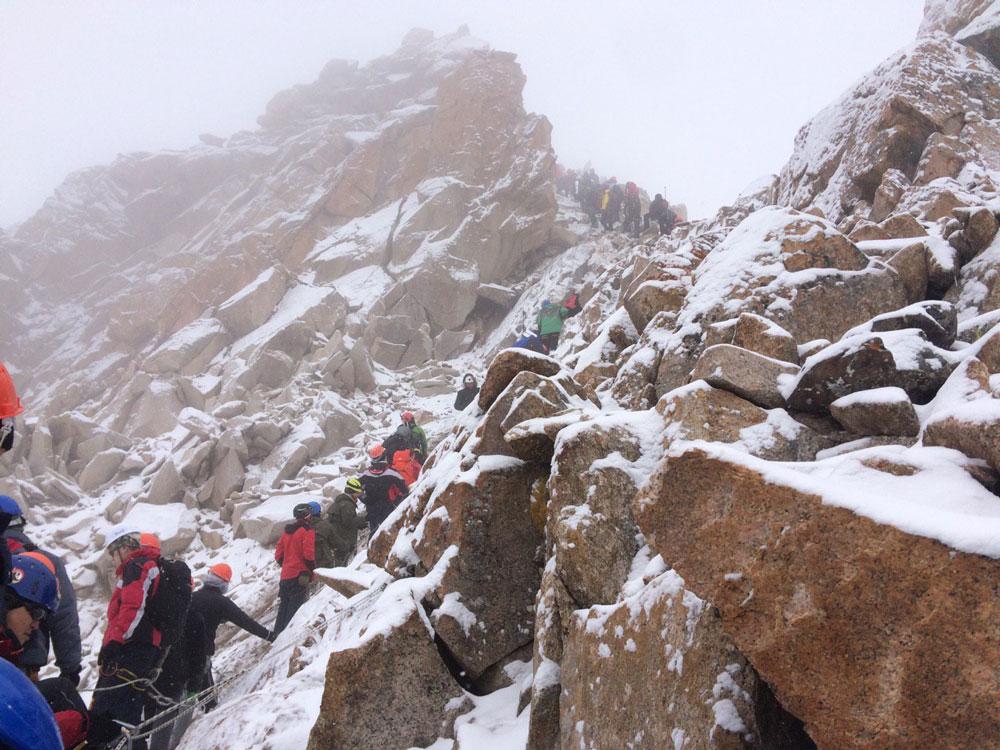 На альпиниаде все пристегиваются к веревочным перилам и идут друг за другом