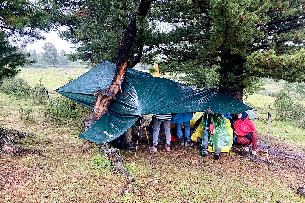 Тент — очень полезная в походе вещь: его можно натянуть между деревьями илина трекинговые палки и переждать дождь
