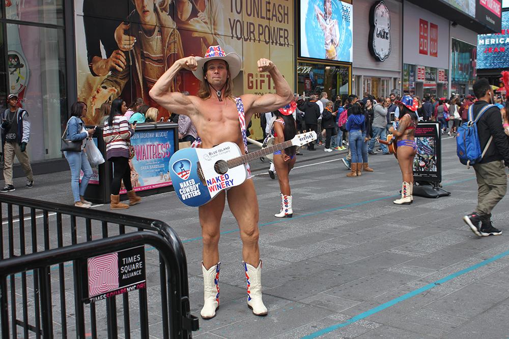 Голый ковбой позирует для фото на Таймс-сквер. Он местная знаменитость. Мужчина зарегистрировал свой товарный знак и даже судился с компанией M&M;'s, которая использовала его образ в рекламе
