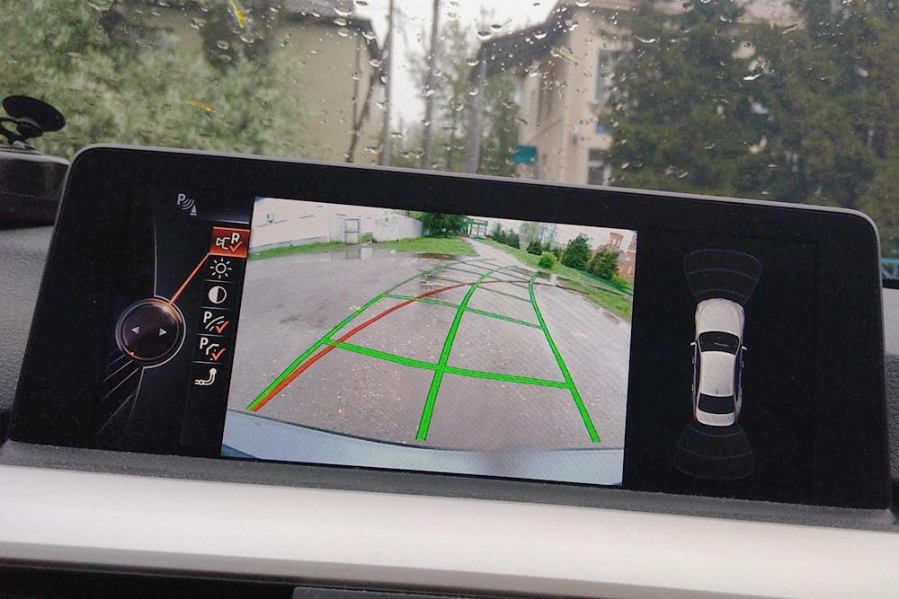 Работа камеры заднего вида. Зеленые линии означают возможную траекторию движения и меняют положение накартинке взависимости отположения руля. Удобно