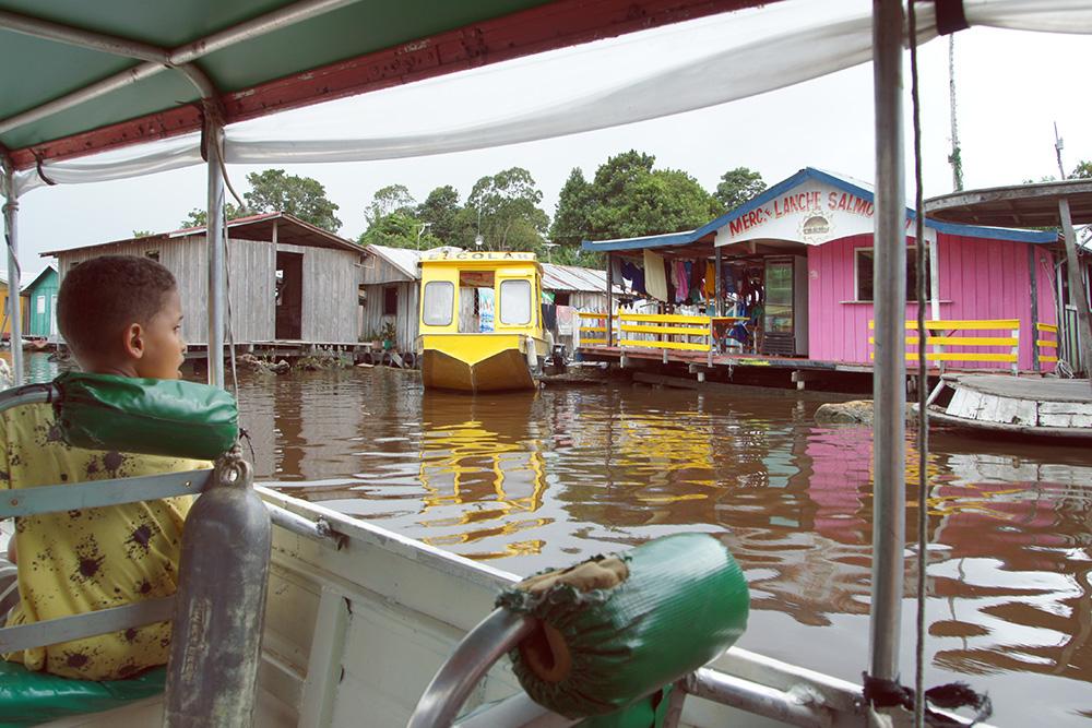 Поселение из плавучих домов в Амазонии. Желтая лодка — аналог школьного автобуса