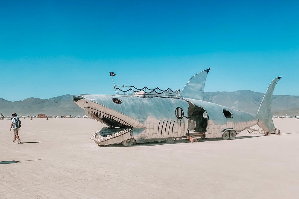 По территории фестиваля ездят самые невообразимые машины. Первые два дня мы сходили с ума, когда их видели. На крыше у этой акулы — обзорная площадка длябернеров. Так называют участников фестиваля