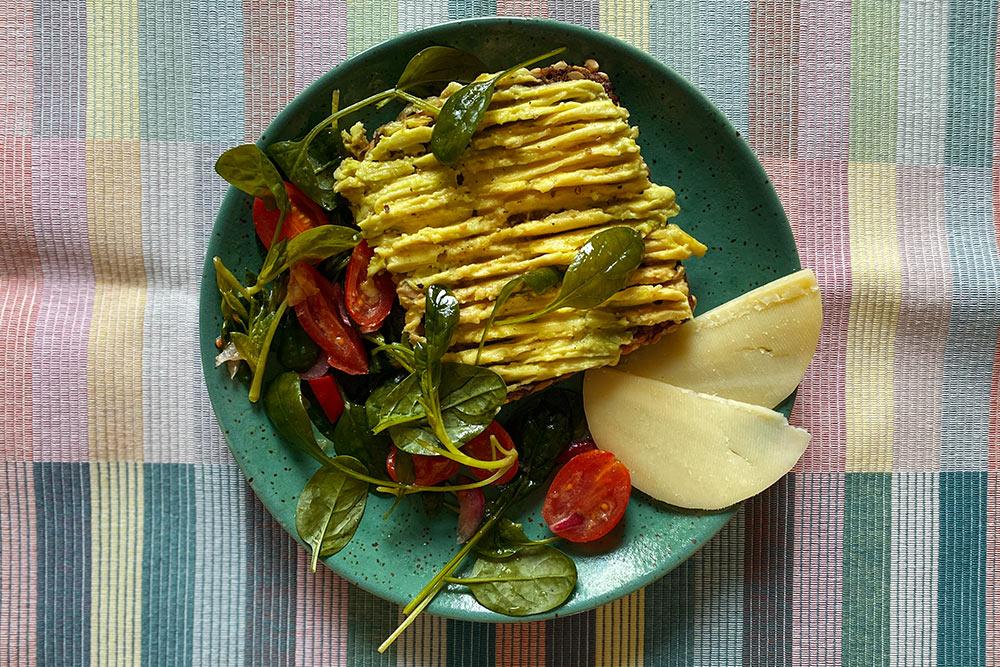 Подсушиваю кусок хлеба, разминаю вилкой авокадо и ем тост с остатками вчерашнего салата и парой ломтиков сыра