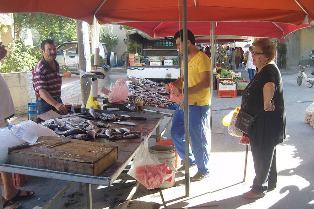 Пенсионерка на деревенском рынке выбирает продукты — как правило, там они дешевле и качественнее